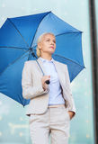 有户外伞的年轻严肃的女实业家 库存照片