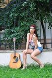 有户外吉他的俏丽的女孩 免版税库存图片