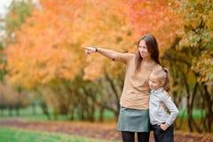 有户外妈妈的小女孩在公园秋天天 图库摄影