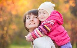 有户外孩子女孩的母亲在金黄秋天backg 库存图片