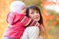 有户外孩子女孩的美丽的母亲在秋天 免版税库存照片