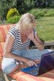 有户外开放笔记本的白肤金发的妇女 免版税库存照片