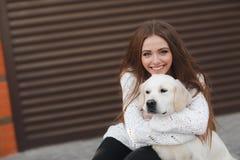 有户外心爱的狗的美丽的妇女 图库摄影