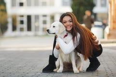 有户外心爱的狗的美丽的妇女 免版税库存图片