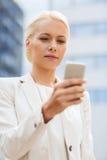 有户外智能手机的严肃的女实业家 免版税库存图片