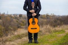 有户外橙色吉他的年轻人 免版税库存图片