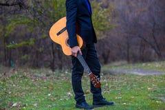 有户外橙色吉他的年轻人 库存图片