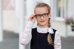 有户外玻璃和校服的年轻女小学生为 库存照片