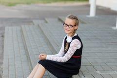 有户外玻璃和校服的年轻女小学生为 库存图片