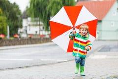 有户外红色伞和五颜六色的夹克的a漂亮的孩子 免版税库存图片