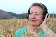 有户外耳机的美丽的自然成熟妇女 享受与拷贝空间的音乐 免版税图库摄影