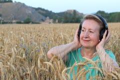 有户外耳机的美丽的自然成熟妇女 享受与拷贝空间的音乐 免版税库存图片
