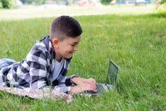 有户外膝上型计算机的年轻男孩 免版税库存图片