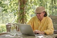 有户外膝上型计算机的老人 免版税库存图片