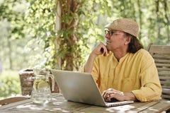 有户外膝上型计算机的老人 库存照片