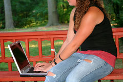 有户外膝上型计算机的青少年的女孩 库存照片
