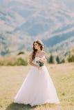 有户外花婚礼花束的美丽的白肤金发的新娘在山背景 免版税库存图片