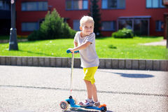 有户外滑行车的小男孩 免版税库存图片