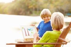 有户外绘风景的孙子的祖母 免版税库存照片