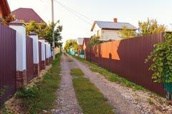 有房子和篱芭的村庄街道 免版税库存照片