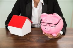 有房子和piggybank的女实业家 免版税库存图片