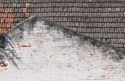 有房子屋顶的老肮脏的砖墙 库存图片