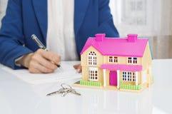 有房子模型和笔签署的合同文件的妇女 免版税图库摄影