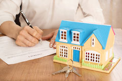 有房子模型和笔签署的合同文件的妇女 免版税库存图片
