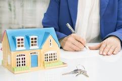 有房子模型和笔签署的合同文件的妇女 库存图片
