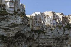 有房子的古镇由在俯视海的白色峭壁的落日点燃了 免版税库存照片