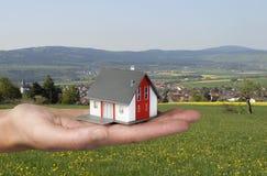 有房子的手在风景前面 库存图片