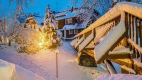 有房子的木桥与光的夜在雪在萨克森瑞士国家公园,B的易北河砂岩山脉 库存照片