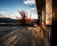 有房子的秋天在太阳的日落光芒的露台和树 免版税库存图片