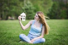 有房子纸板形象的女孩  免版税图库摄影
