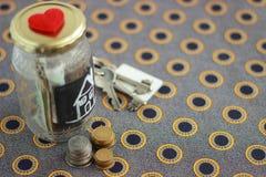有房子钥匙的金钱瓶子 库存照片