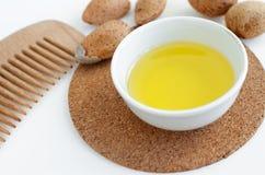 有扁桃仁油和木头发梳子的小碗自然头发的 免版税库存照片