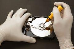 有手套修理硬盘的手 库存图片