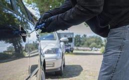 有手套的一个人设法打破汽车的锁 免版税库存图片