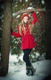 有手套的可爱的白肤金发的女孩,红色摆在冬天的外套和红色帽子下雪。冬天风景的美丽的妇女。少妇 免版税库存照片