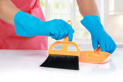 有手套的手使用清扫清洁的笤帚 免版税图库摄影