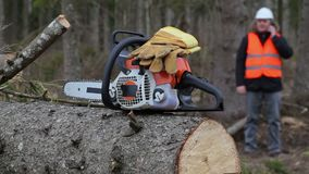 有手套的锯在背景伐木工人谈话在巧妙的电话 股票视频