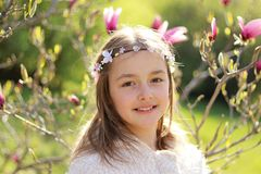 有手工制造头发花圈的美丽的小女孩在微笑她的头看照相机在开花的春天庭院里 免版税库存照片