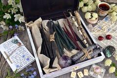 有手工制造蜡烛、水晶、诗歌、花和魔术的巫婆箱子反对 库存图片