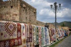 有手工制造装饰品的地毯在英王乔治一世至三世时期城市的街道上垂悬待售 图库摄影