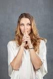 有手指的可爱的少妇在嘴唇 库存照片