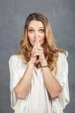 有手指的可爱的少妇在嘴唇 免版税库存照片
