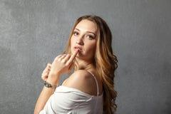 有手指的可爱的少妇在嘴唇 免版税库存图片