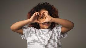 有手指的在心脏形状,演播室画象愉快的矮小的黑人女孩 库存图片