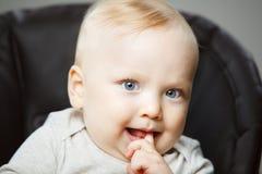 有手指的宜人地惊奇的男婴在嘴 库存图片