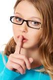 有手指的少年妇女在嘴唇 免版税库存图片